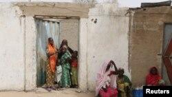 Des femmes observent une patrouille militaire camerounaise à Kerawa, au Cameroun, à la frontière avec le Nigeria, le 16 mars 2016.