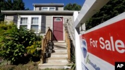 "FILE - A ""For Sale"" sign hangs in front of a house in Walpole, Massachusetts."