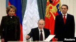 ولادیمیر پوتین رئیس جمهوری روسیه در حال امضای لایحه الحاق شبه جزیره کریمه به روسیه در مراسمی در پارلمان - مسکو، ۲۱ مارس ۲۰۱۴