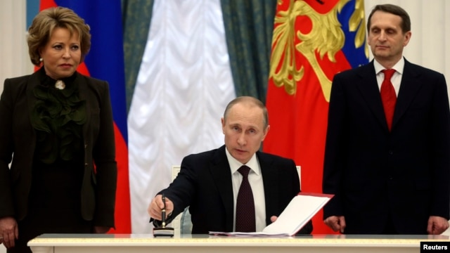 Russian President Vladimir Putin signs legislation completing the process of absorbing Crimea into Russia during a Kremlin ceremony in Moscow on March 21, 2014.