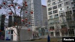 2020年2月18日星期二,只見一位戴口罩的女性在北京市中心商業區一座商業大樓前走過。