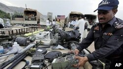 A Pakistani officer in Peshawar arranges recovered equipment that has been stolen in recent months from NATO forces fighting in neighboring Afghanistan, 27 Sep 2010