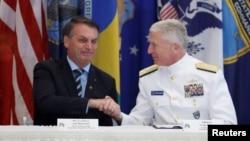 Presiden Brazil Jair Bolsonaro (kiri) dan Laksamana AS Craig Faller menandatangani perjanjian pertahanan Brazil-AS di Miami, Florida, Minggu (8/3).