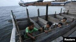 Anak-anak memakai WC umum di atas laut di daerah kumuh dekat pelabuhan Jakarta. (Foto: Reuters/Beawiharta)