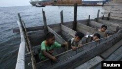 Anak-anak menggunakan toilet dari kayu di daerah kumuh dekat pelabuhan Jakarta Utara. (Foto: Reuters/Beawiharta)