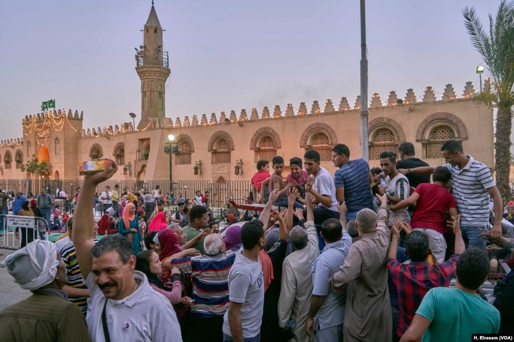 Люди раздают еду, воду и напитки мусульманам, приезжающим на молитвы в мечеть Амр ибн аль-Ас, в старый Каир, Египет, 31 мая 2019 года.