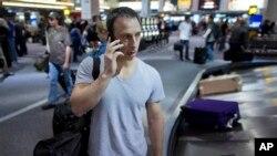 Seorang penumpang menelepon saat mengambil bagasinya di Bandara Internasional McCarran International di Las Vegas. (AP/Julie Jacobson)