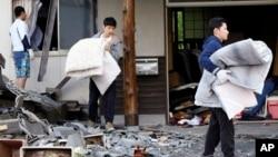 지난 17일 일본 구마모토 현 미나미아소 시 주민들이 지진으로 무너진 가옥에서 이불을 꺼내고 있다.