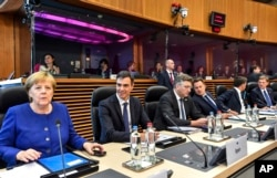 German Chancellor Angela Merkel, left, along with other EU leaders, attends a roundtable meeting at an informal EU summit on migration at EU headquarters in Brussels, June 24, 2018.