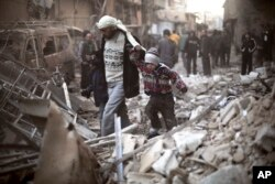 FILE - A man walks with a pair of children in hand through the rubble in Eastern Ghouta, Syria, Dec. 24, 2015.