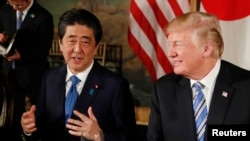 FILE - President Donald Trump looks on as Japan's Prime Minister Shinzo Abe speaks while dining at Trump's Mar-a-Lago estate in Palm Beach, April 18, 2018.