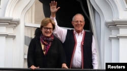 Peruvian presidential candidate Pedro Pablo Kuczynski (R) next to his wife Nancy Lange waves to followers from his house, in Lima, Peru, June 6, 2016.