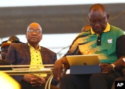 FILE - Newly elected ruling African National Congress (ANC) party president, Cyril Ramaphosa, right, and former ANC president and South African President Jacob Zuma, left, attend the party's 106th birthday celebrations in East London, South Africa, Jan. 13, 2018.