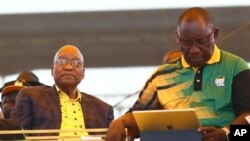 FILE - Newly-elected ruling African National Congress (ANC) party president, Cyril Ramaphosa, right, and former ANC president and South African President Jacob Zuma, left, attend the party's 106th birthday celebrations in East London, South Africa, Jan. 13, 2018.