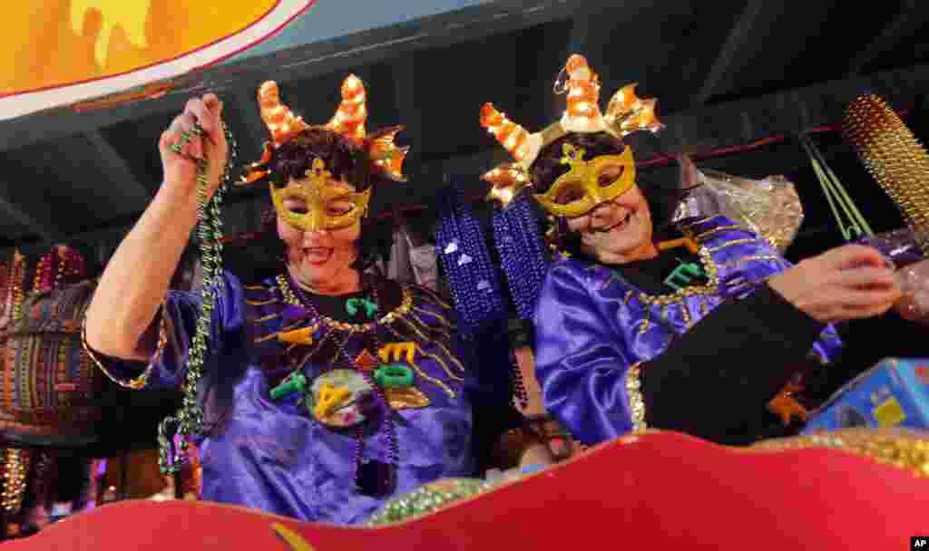 Personas en carrozas flotantes lanzan adornos durante el desfile Mardi Gras de Krewe of Cleopatra en Nueva Orleáns, el viernes 2 de febrero de 2018. Aunque la temporada de Carnaval comenzó oficialmente el 6 de enero, las festividades realmente se aceleran los dos fines de semana antes del Fat Tuesday. Este año Fat Tuesday es el 13 de febrero. (AP Photo / Gerald Herbert)
