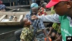 Wani magidanci ya kawo dansa cikin kwale-kwale ana diga masa maganin rigakafin Polio a yankin Niger-Delta na Najeriya