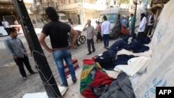 叙利亚人站在被桶装炸弹炸死者的尸体旁(2015年5月30日)
