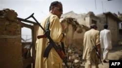 Загін народного ополчення Лашкар, яке бореться проти Талібану проходить серед зруйнованих будинків у селищі Султанвас у регіоні Бунер, Пакистан.