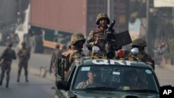 Army troops secure a road leading to the site of suicide bombing in Rawalpindi, Jan. 20, 2014.