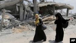 이스라엘과 하마스가 휴전에 돌입한 가운데, 5일 팔레스타인 여성들이 폭격으로 부서진 집에서 찾은 물건을 나르고 있다.