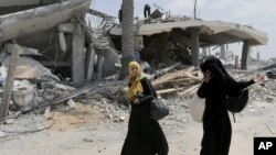 Dua orang perempuan Palestina berjalan di antara reruntuhan di Gaza, sementara gencatan senjata 72 jam bertahan di sana (6/8).