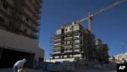 A construction worker works at a site of a new housing unit in the east Jerusalem neighborhood of Har Homa, Wednesday, Nov. 2, 2011.