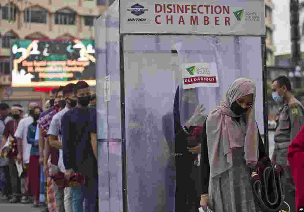 Muslims line up to enter a disinfection room set up to protect against the new coronavirus outbreak, before entering Al Mashun Grand Mosque to attend an Eid al-Adha prayer in Medan, North Sumatra, Indonesia.