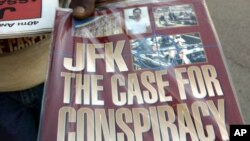 FILE - A vendor displays a booklet alleging a conspiracy was behind the assassination of President John F. Kennedy in downtown Dallas, Saturday, Nov. 8, 2003.