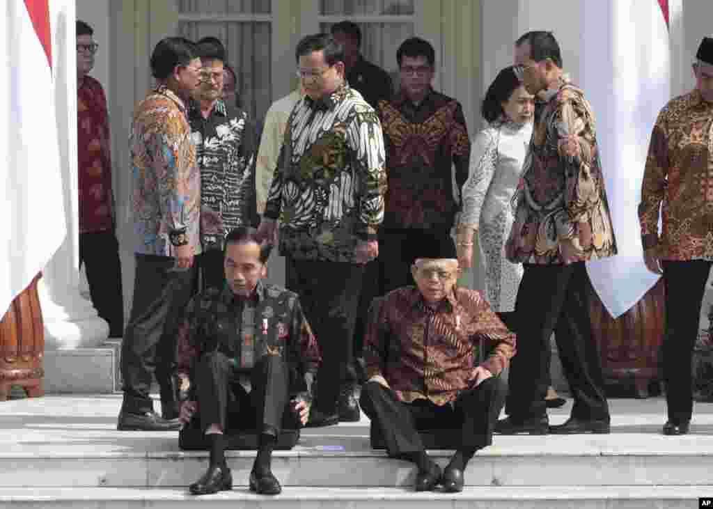 Menteri PertahananPrabowo Subianto (tengah) berjalan melewati Presiden Joko Widodo dan Wakil Presiden Ma'ruf Amin yang sedang duduk di tangga saat pengumuman susunan kabinet baru di Istana Merdeka, Jakarta, Rabu, 23 Oktober 2019. (Foto: Dita Alangkara/AP)