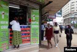 FILE - Pedestrians walk past an M-Pesa shop in downtown Nairobi, Kenya, May 12, 2009.