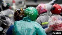 Seorang penumpang menggunakan helm Grab di Jakarta (1/2). (Reuters/Darren Whiteside)