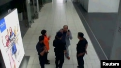 A still image from a CCTV footage appears to show a man purported to be Kim Jong Nam talking to security personnel, after being accosted by a woman in a white shirt, at Kuala Lumpur International Airport in Malaysia, Feb. 13, 2017. (FUJI TV/via Reuters)