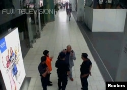 FILE - A still image from a CCTV footage appears to show a man purported to be Kim Jong Nam talking to security personnel, after being accosted by a woman in a white shirt, at Kuala Lumpur International Airport in Malaysia, Feb. 13, 2017.