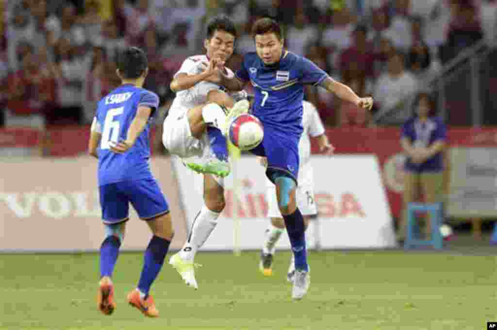Ko Oo Ye of Myanmar, second left, and Thitipan Puangjan of Thailand, right, vie for the ball during the soccer final match at the SEA Games in Singapore, Monday, June 15, 2015. (AP Photo/Joseph Nair)