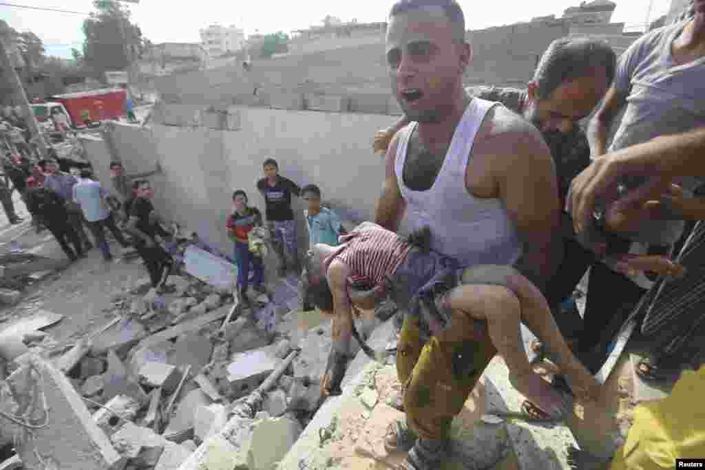 A Palestinian man carries the body of Palestinian girl killed in an Israeli airstrike in Khan Younis, in the southern Gaza Strip, July 29, 2014.