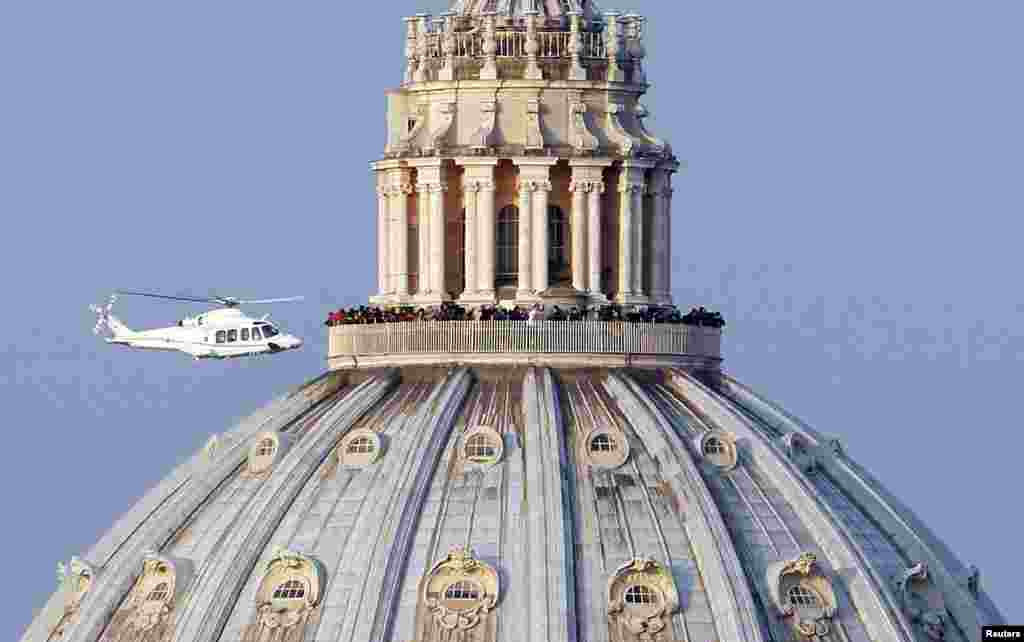 "A helicopter carrying Pope Benedict XVI takes off from inside the Vatican on its way to the papal summer residence at Castel Gandolfo. Pope Benedict slips quietly from the world stage after a private last goodbye to his cardinals and a short flight to a country palace to enter the final phase of his life ""hidden from the world""."