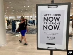 FILE - A customer walks behind a sign at a Nordstrom store seeking employees in Coral Gables, Fla., May 21, 2021.