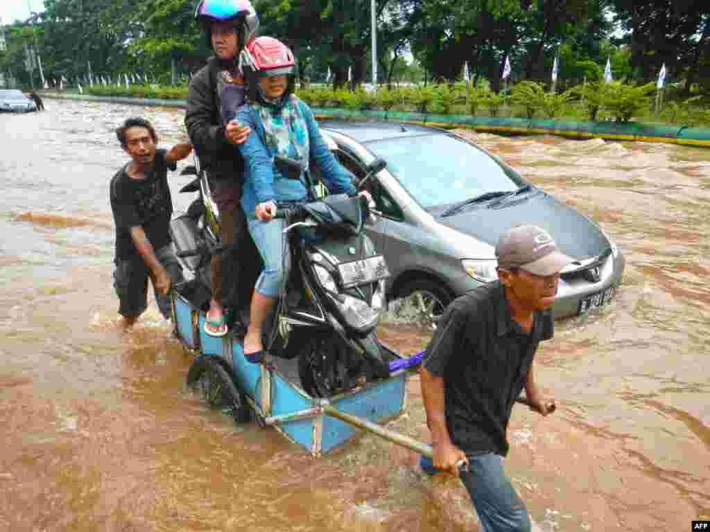 A couple sitting on their motorcycle cross a flooded road on a cart in Jakarta. Heavy monsoon rains have flooded many sections of the Indonesian capital leaving some commuters stranded.