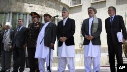 Afghan President Hamid Karzai, 3rd right, speaks to the media, supported by members of his cabinet at the presidential palace in Kabul, Afghanistan, on Thursday, June 23, 2011. Afghan President Hamid Karzai says his nation's youth will stand up and defend