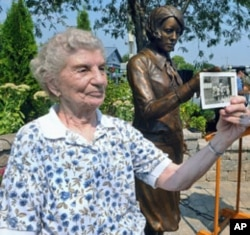 Next to the 'Radium Girls' statue, Rose Baima, who worked at Luminous Process, holds a photo of her and her co-workers during the 1940's, September 2, 2011.