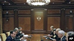 Russian President Dmitry Medvedev, left, speaks to US Defense Secretary Robert Gates, second right, during their meeting at which they discussed the planned missile defense system in Europe, at the Gorki residence outside Moscow, March 22, 2011