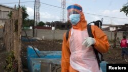 A health worker prepares to disinfect a van used for burial purposes in Freetown, Sierra Leone, Nov. 10, 2014.