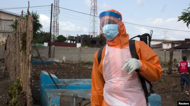 FILE - A health worker prepares to disinfect a van used for burial purposes in Freetown, Sierra Leone.