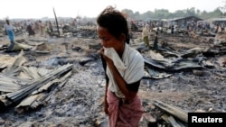 A woman walks among debris after fire destroyed shelters at a camp for internally displaced Rohingya Muslims in the western Rakhine State near Sittwe, Myanmar.