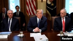 FILE - U.S. President Donald Trump speaks during a cabinet meeting, flanked by Secretary of State Rex Tillerson, left, and Secretary of Defense James Mattis, right, at the White House in Washington, Nov. 1, 2017.