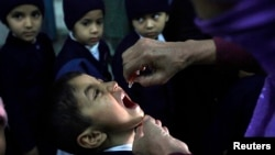 FILE - A female polio worker gives polio vaccine drops to a child in Lahore.