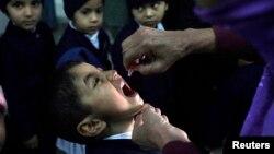 2012年12月﹐一名女工作人員在巴基斯坦拉合爾為當地兒童進行小兒麻痺症預防工作。
