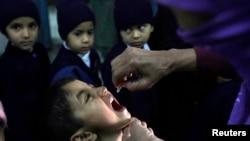 파키스탄 라호르에서 여성 보건 요원이 어린이에게 소아마비 백신을 주고 있다 (자료사진)