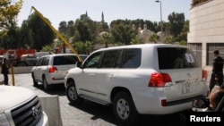 FILE - U.N. vehicles, transporting a team of experts from the Organization for the Prohibition of Chemical Weapons, leave their hotel in Damascus October 22, 2013.