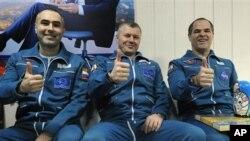 Kosmonot Rusia Yevgeny Tarelkin (kiri), Oleg Novitsky (tengah) dan astronot NASA Kevin Ford berpose di bandara Kostanai, Kazakhstan seusai pendaratan dengan kapsul Soyuz (16/3).